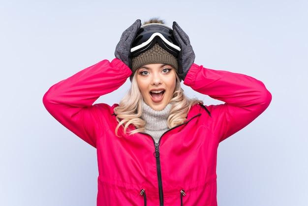 Skiër tiener meisje met snowboard bril over geïsoleerde blauw met verrassing gelaatsuitdrukking