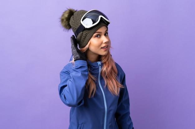 Skiër tiener meisje met snowboard bril over geïsoleerde paarse achtergrond luisteren naar iets door hand op het oor te leggen