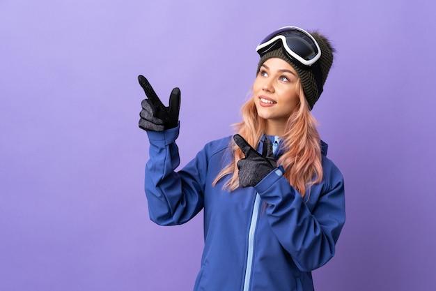 Skiër tienermeisje met snowboard bril over geïsoleerde paarse achtergrond met de wijsvinger een geweldig idee