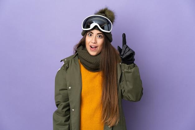 Skiër vrouw met snowboard bril geïsoleerd op paarse muur van plan om de oplossing te realiseren terwijl het opheffen van een vinger