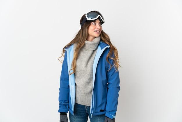 Skiër vrouw met snowboard bril geïsoleerd op wit een idee denken terwijl opzoeken