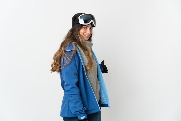 Skiër vrouw met snowboard bril geïsoleerd op wit handen uitbreiden naar de zijkant