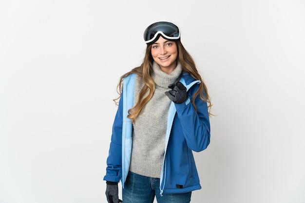 Skiër vrouw met snowboard bril geïsoleerd op wit verrast en wijst naar voren