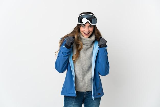 Skiër vrouw met snowboard bril geïsoleerd op wit vieren een overwinning in winnaarspositie