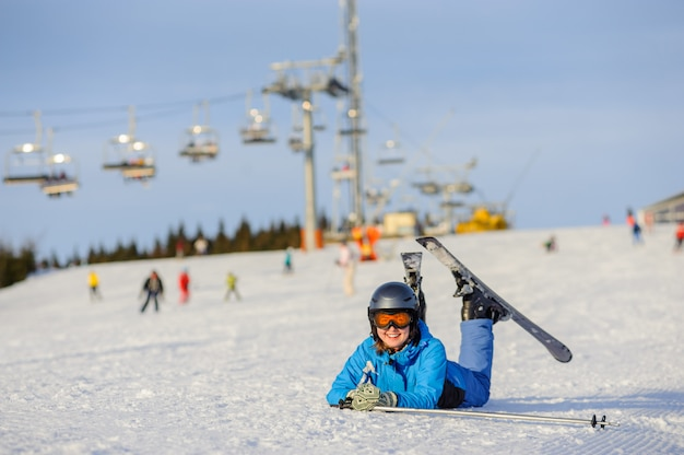 Skiërmeisje die op de sneeuw bij skitoevlucht liggen op een zonnige dag