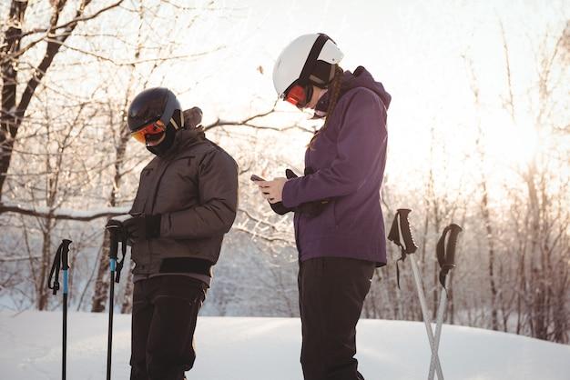 Skiërpaar dat mobiele telefoon met behulp van