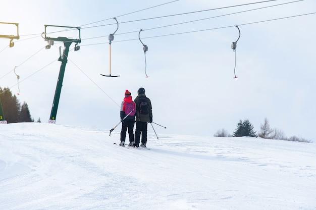 Skiërs beklimmen de helling bij de skiliften
