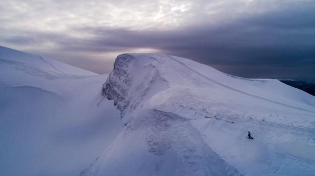 Skiërs bovenop. geweldige luchtfoto van een heuvel bedekt met een dikke laag sneeuw op een bewolkte mistige dag