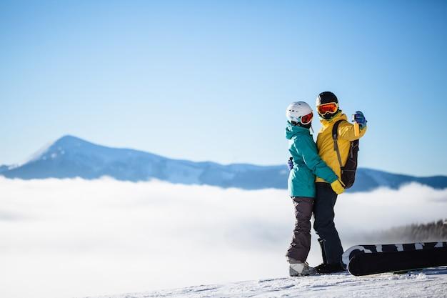 Skiërs die een foto van zichzelf maken met een smartphone over een berg
