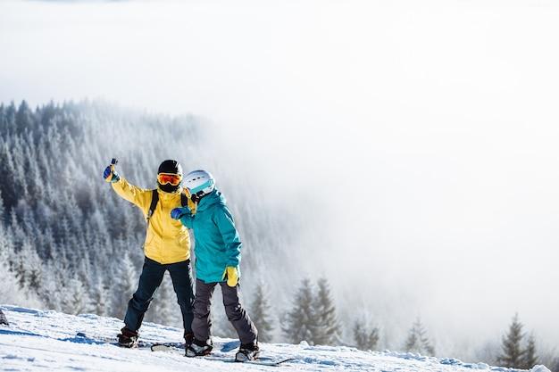 Skiërs die een foto van zichzelf nemen met een slimme telefoon over een berg