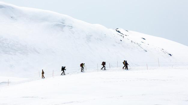 Skiërs die op sneeuw behandelde bergketens lopen