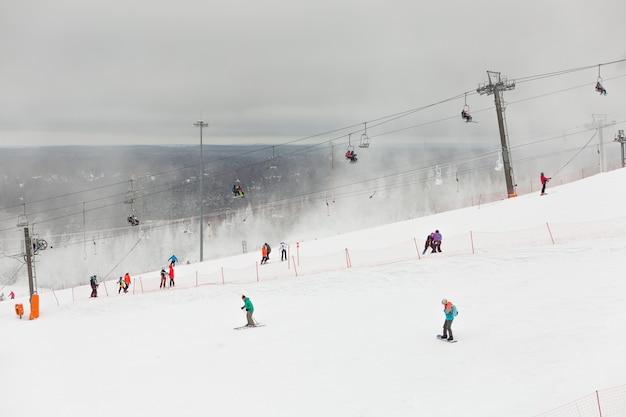 Skiërs en snowboarders op de helling van winterresort in sint-petersburg, rusland.