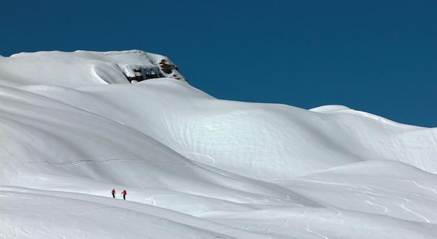 Skiërs in een zwaar ingesneeuwde bergen.