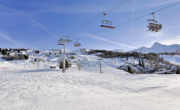 Skiërs op stoeltjesliften in alpine resort op wintersport