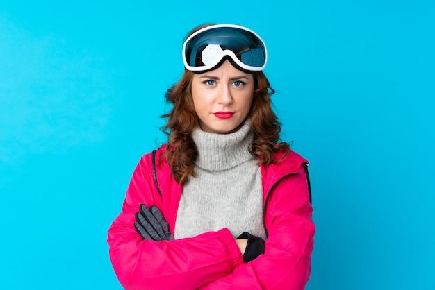 Skiërvrouw die met snowboardglazen wapens gekruist houden
