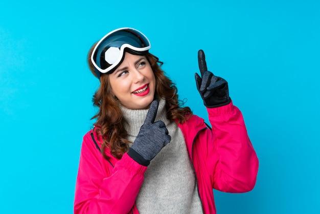 Skiërvrouw met snowboardglazen over geïsoleerde blauwe muur die met de wijsvinger een groot idee richten