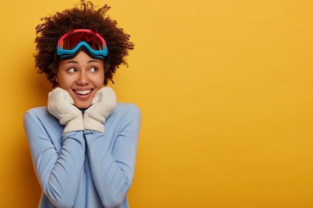Skigebied en snowboarden. blij dat lachende vrouw met donkere huid witte handschoenen draagt, skibril en blauwe coltrui draagt, staat op gele achtergrond