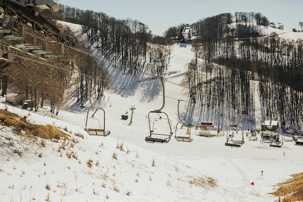 Skigebied, helling, skiërs op de piste onder witte sneeuw.