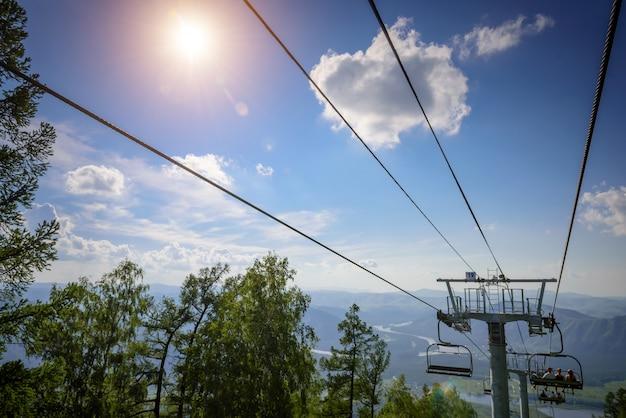 Skilift in de bergen op zonnige dag tegen blauwe hemel, witte wolken, groene heuvels en bergmeer. bergdal met kabelbaan, uitzicht vanaf de top. skigebied in de zomer.