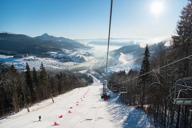 Skilift met skiërs, besneeuwde helling, bergen met een ideaal landschap van besneeuwd terrein en nevel erover op een zonnige dag in het resort. skiseizoen en wintersport concept