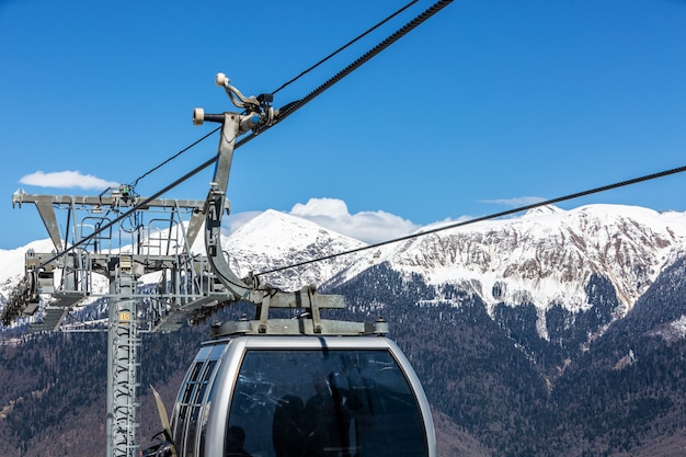 Skilift met stoelen die over de berg gaan en paden van luchten en snowboards