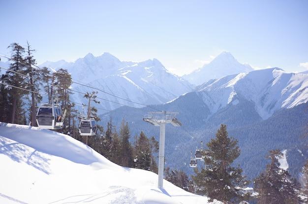 Skilift met stoelen die over de berg gaan en paden vanuit luchten en snowboards.