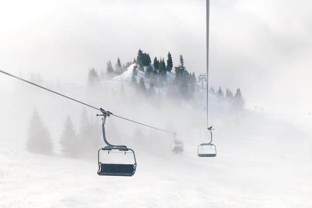 Skilift op de achtergrond van bergen in de mist. mooie luxe beste wintervakantie concept achtergrond.