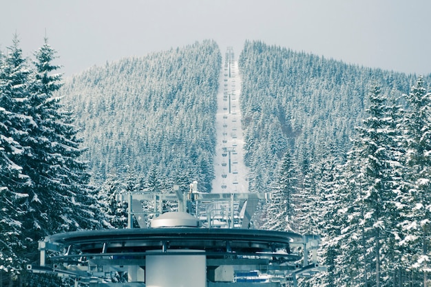 Skiliftwiel met berg- en bewegende sporters; focus op voorgrondwiel en bos