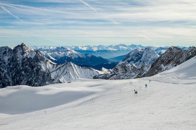 Skipiste en panorama van de besneeuwde alpen vanuit het skigebied