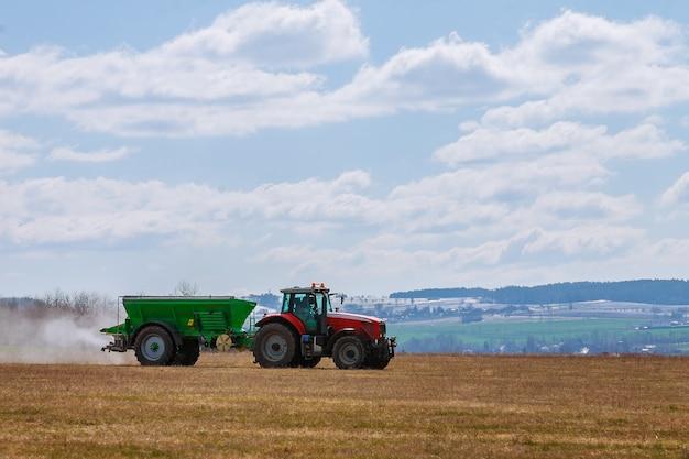 Skutc, tsjechië - 23 maart 2020: trekker die kunstmest verspreidt op grasveld. landbouw werk.