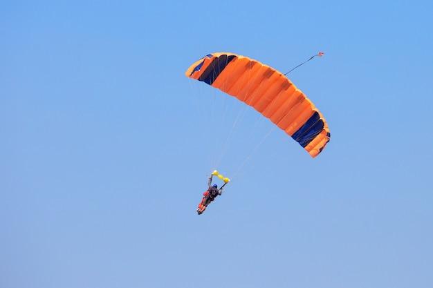 Skydiver onder een oranje parachute