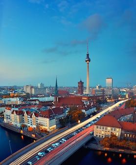 Skyline van berlijn in duitsland na zonsondergang met brug over de rivier de spree, het centrum van gebouwen en de alexandrplatz tv-toren.