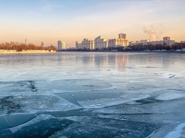 Skyline van de stad over een rivier bedekt met ijs. zonlicht op een winteravond bij zonsondergang. uitzicht vanaf de rivierdijk.