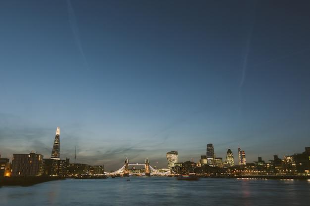 Skyline van londen in de schemering met rivier de theems op de voorgrond