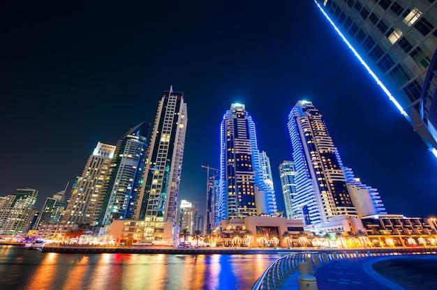 Skylinesmening die van de jachthaven van doubai in nacht tonen