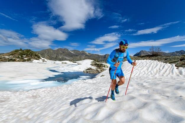 Skyrunner man bergop in een besneeuwde stuk