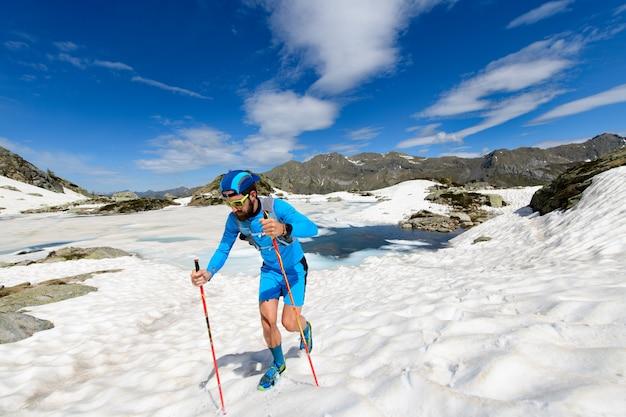 Skyrunner man in actie bergop gaan op sneeuw