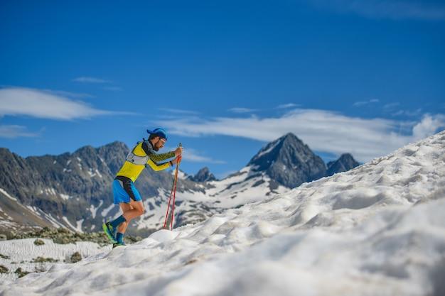 Skyrunning opleiding met stokken op de sneeuw bergopwaarts