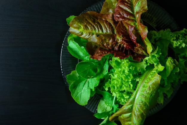 Sla en rucola bladeren op zwarte houten tafel, biologisch voedsel, vegetarisme.