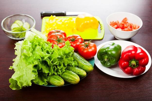 Sla met komkommers, tomaten, paprika, snijplank en mes op tafel.