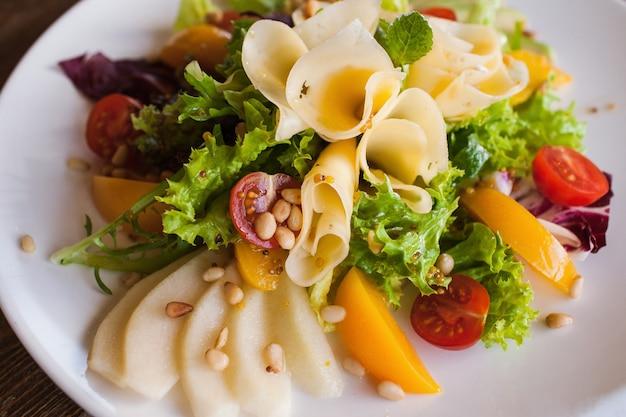 Sla salade met kaas en fruit op plaat.