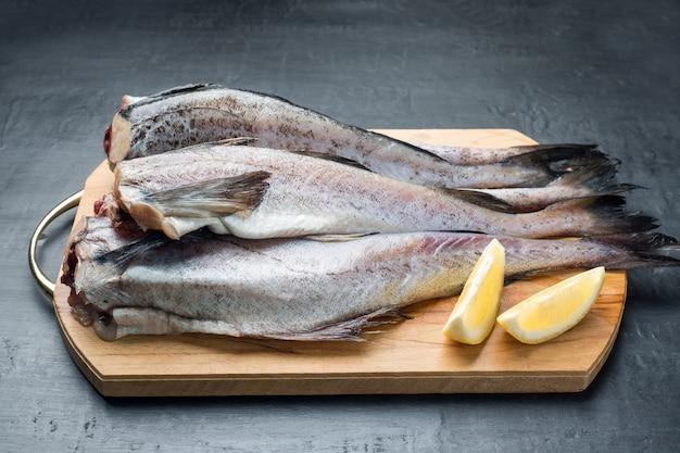 Slaaf rauwe vis op een houten snijplank, citroen en pepermix