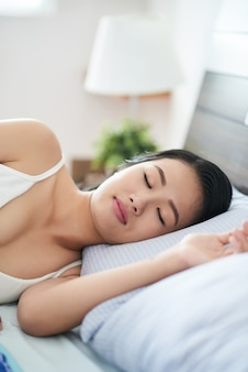 Slaap aziatische vrouw op bed