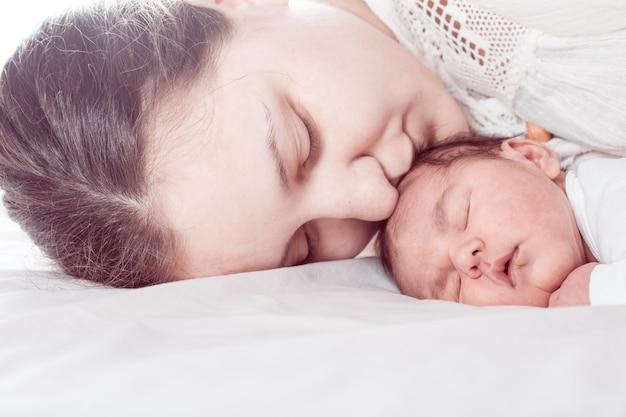 Slaap baby met mama, close-up gezichten, mama's kus