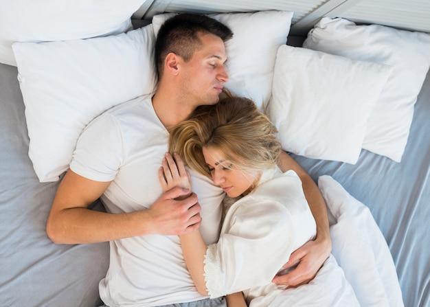 Slaap jong paar knuffelen op bed