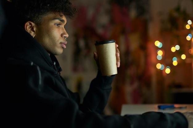 Slaap nodig doordachte jonge kerel met piercing die een wegwerp kopje koffie vasthoudt terwijl hij aan de tafel zit