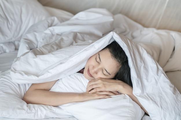 Slaap van de close-up de aziatische vrouw op bed onder deken in slaapkamer