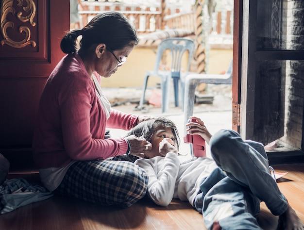 Slaap van het kindmeisje op schoot van moeder