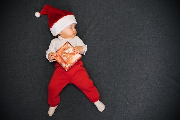 Slaapjongen in de hoed van de kerstman ligt met een geschenkdoos