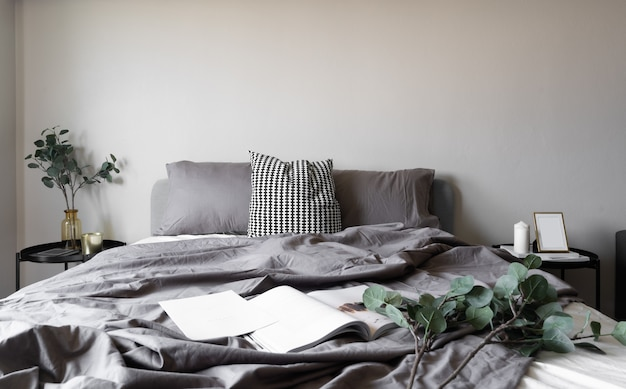 Slaapkamer hoek zachte kussens instelling versierd met ronde nachtkastje en met gouden fotolijst op beige geschilderde muur